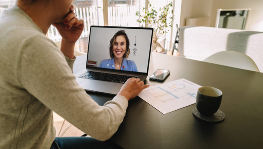 Woman teleconferencing with female colleague on laptop