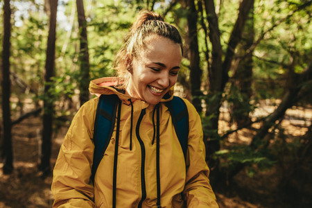 Woman with backpack standing in forest and smiling