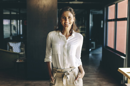 Confident entrepreneur standing in office