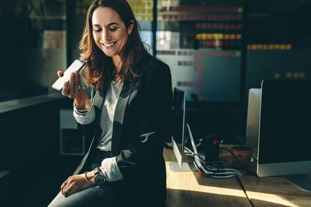 Female executive talking on speaker phone