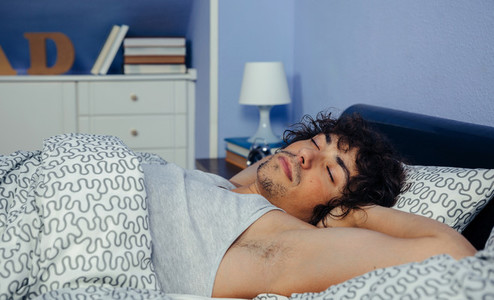 Man sleeping in bed at home