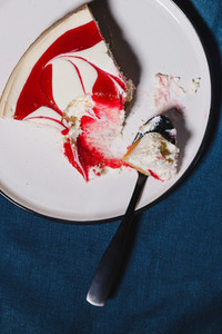 Creative minimalist food photography strawberry cheesecake on a white plate with spoon over dark blue background