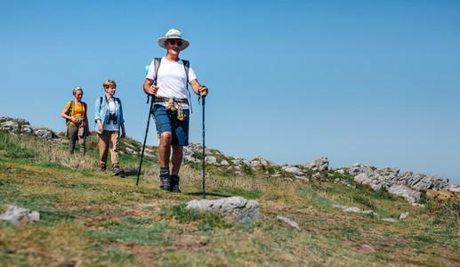 Three people practicing trekking outdoors