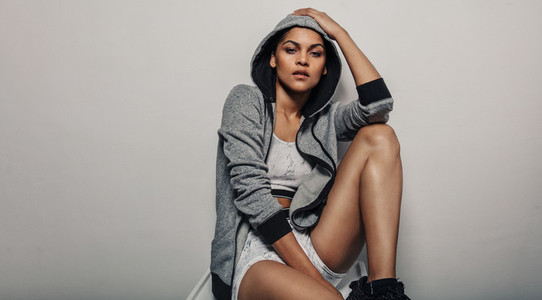 Sporty woman in grey hoodie sportswear
