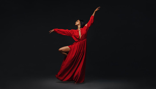 Woman dancing gracefully on black background