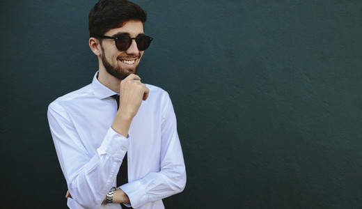 Businessman in sunglasses looking away and smiling