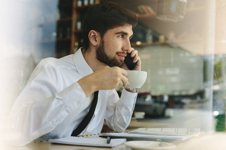 Businessman having coffee and talking on phone at cafe