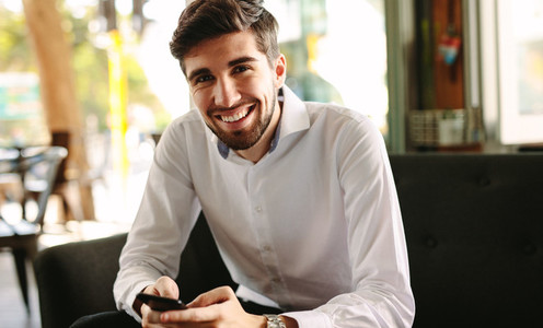Smiling businessman at coffee shop in morning