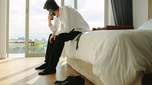 Businessman making phone call while getting ready for office