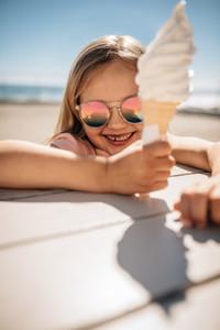 Cute girl having ice cream at the beach