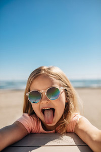 Playful girl at the beach sticking out her tongue