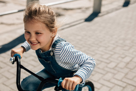 Small girl enjoying riding her bike outdoors