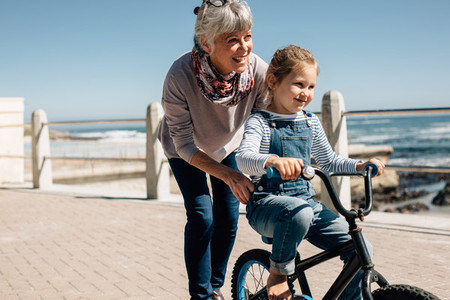 Senior woman helping her granddaughter learn to ride a bicycle