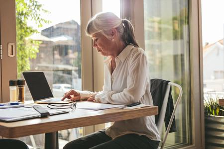 Senior businesswoman working on laptop at coffee shop