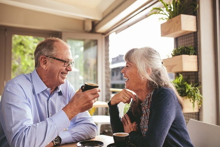 Cheerful senior couple talking over a cup of coffee at cafe