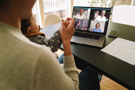 Woman at home video conferencing with colleagues