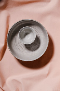 Abstract minimalist still life composition with ceramics over pink cloth