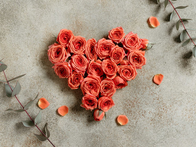 Heart is made from fresh mini coral roses on a beige textured background