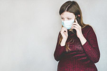Young pregnant woman wearing a face mask