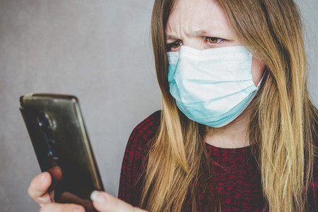 Young woman wearing a face mask and reading in her smart phone