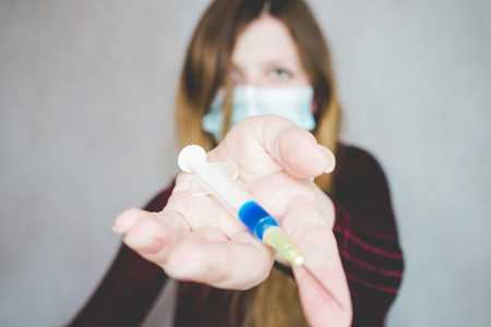 Young woman wearing a face mask and hold a vaccine