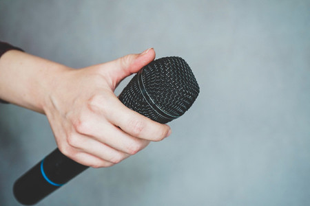 Hand holding a microphone against gray background