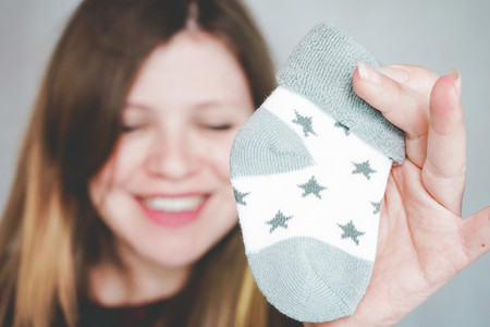 Young pregnant woman holding baby socks