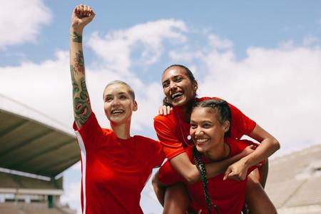Teammates celebrating victory holding the goal scorer