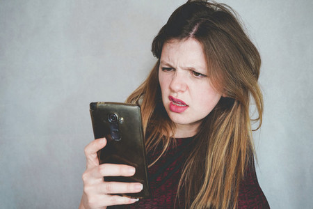 Young woman reading fake news in her smart phone