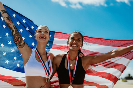 Woman athletes holding up american flag after victory
