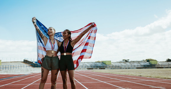Female athletes celebrating victory holding american flag
