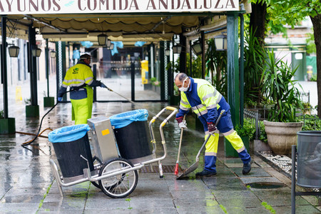 GRANADA SPAIN 23RD APRIL 2020 Sweepers cleaning the streets with coronavirus protection masks