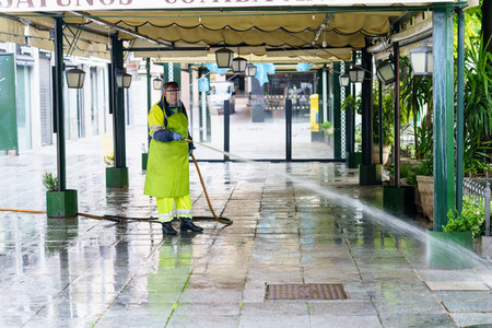 GRANADA SPAIN 23RD APRIL 2020 Sweeper cleaning the street with water pressure hose