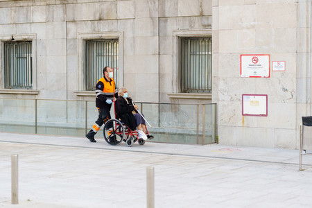 GRANADA SPAIN 23RD APRIL 2020 Sanitary man taking an elderly woman in a wheelchair to the hospital