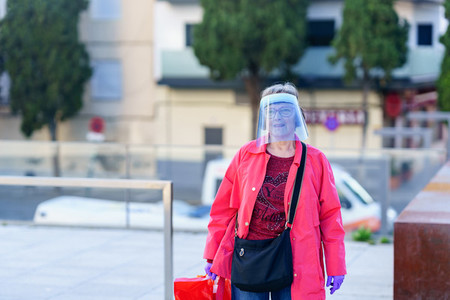 GRANADA SPAIN 23RD APRIL 2020 Older woman shopping in the city protected by a mask
