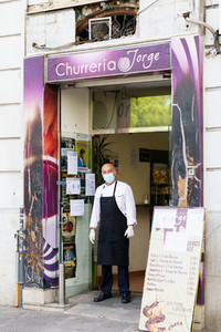 GRANADA SPAIN 23RD APRIL 2020 Cooking a churro shop standing in the doorway of his shop wearing a mask