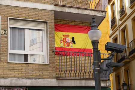 GRANADA  SPAIN  23RD APRIL  2020 Flag of spain with black ribbon on the balcony of a house