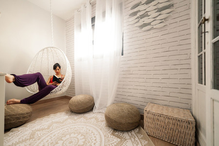 Woman reading a book in a hammock in her bedroom