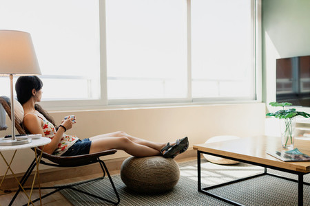 Young woman siting in front of the window in her apartment