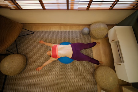 woman practicing yoga in her apartment in front of the window