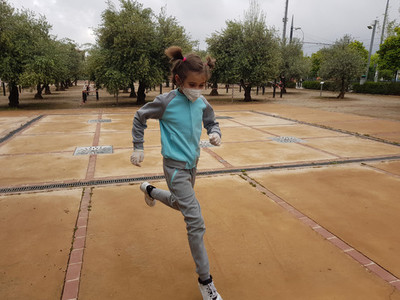 Nine year old girl wearing an N95 mask running in the street