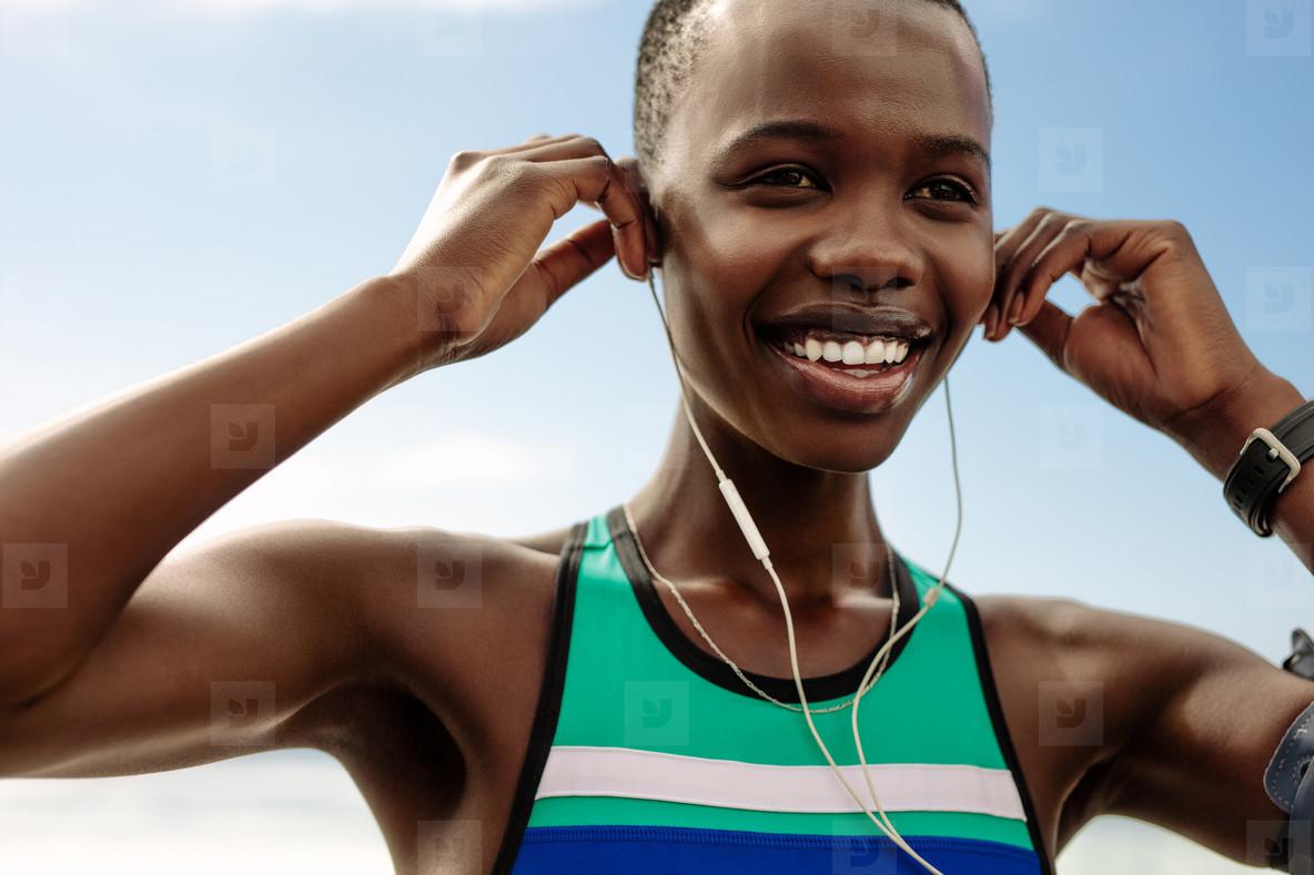 Smiling female runner adjusting her earphones
