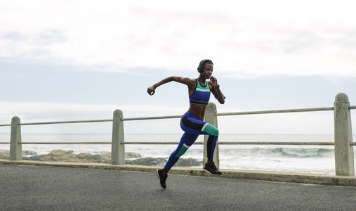 Athletic woman running on seaside promenade