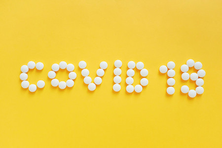 Flat lay of medicine pills shape as word covid 19 on yellow back