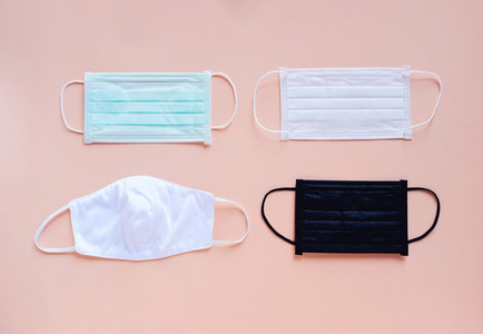 Flat lay of various kind and color of hygienic masks on bright p