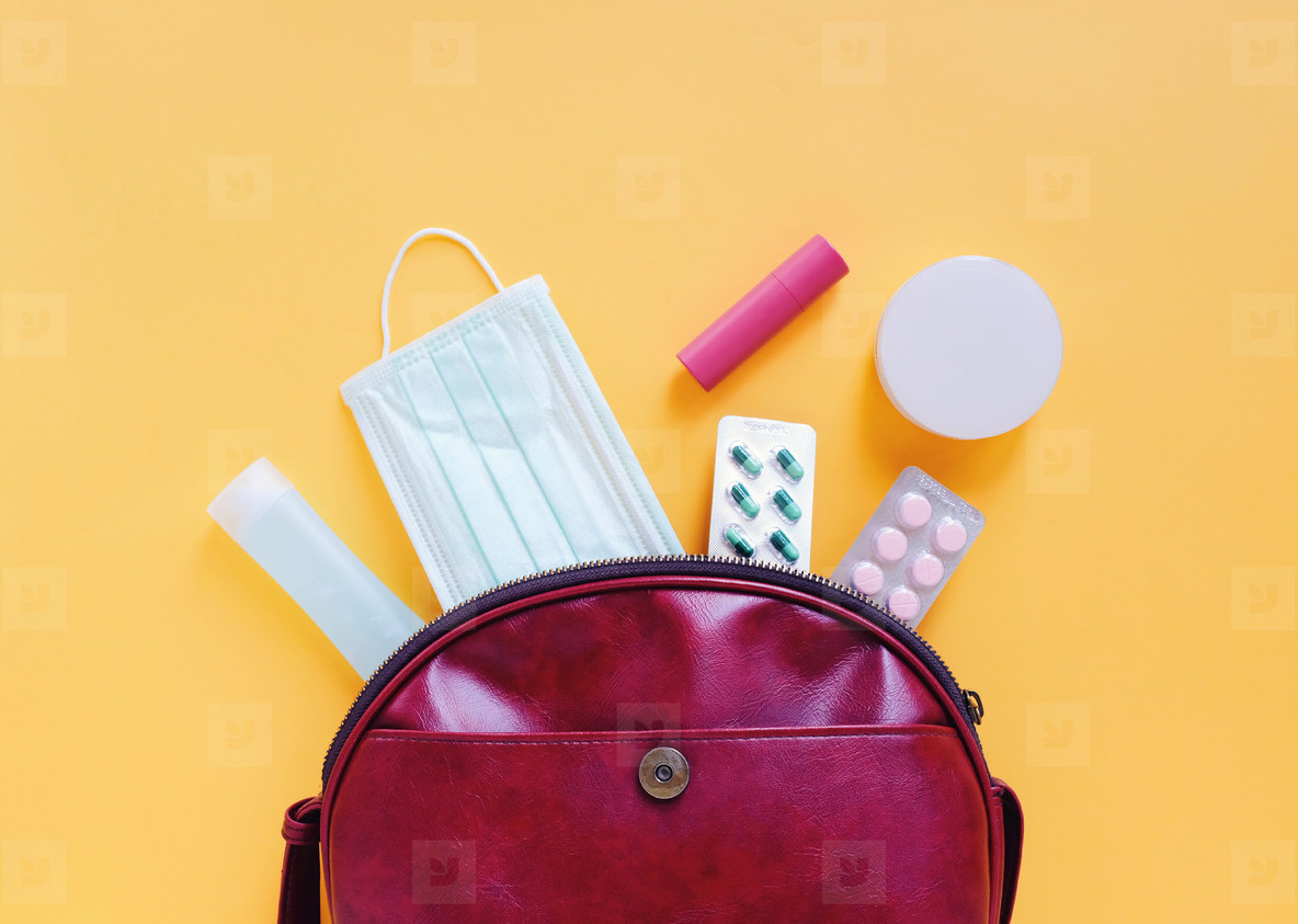 Flat lay of red leather woman bag open out with cosmetics  acces