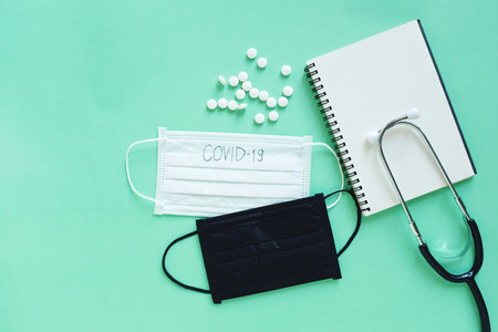 Flat lay of medicine pills mask blanl notebook and stethoscope