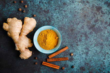 Ingredients for preparation turmeric latte  Curcuma  ginger  cinnamon and allspice on a blue background