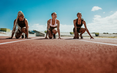 Female athletes ready to start a race on stadium track