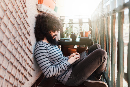Young afro caucasian with laptop in his balcony